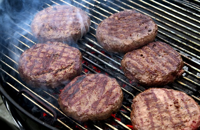 Gourmet beef steak burgers sizzling on a BBQ